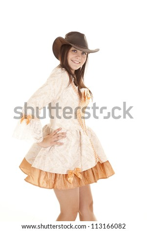 A woman standing in her orange short dress with her hat on her head. - stock photo
