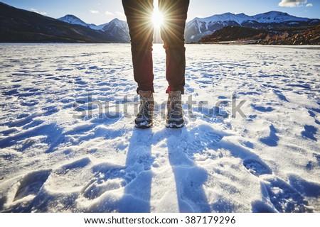 a woman standing on a frozen mountain lake - stock photo