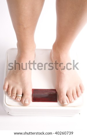 A woman standing on the scale with her bare feet. - stock photo