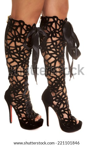 A woman standing sideways showing off her original boots. - stock photo