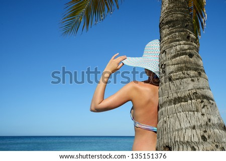 A woman standing under a palm tree watching the ocean. - stock photo