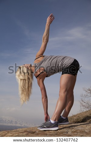A woman standing up on a rock stretching out in her shorts and tank. - stock photo