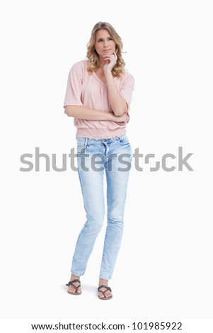 A woman standing up resting her head on her hand is thinking against a white background - stock photo