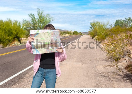 A woman stands along side a remote deserted road reading a map. - stock photo
