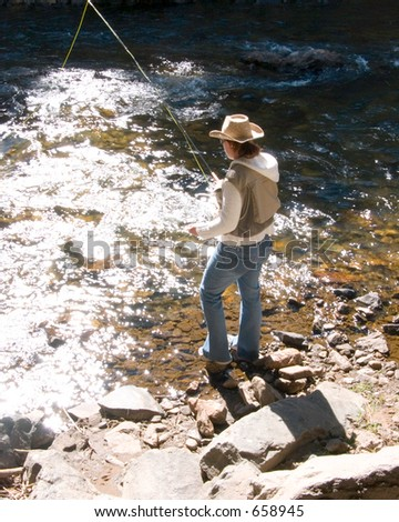 A woman stands in the riverbed casting the bait for a hungry fish. - stock photo