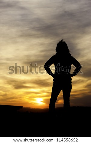 A woman stands with her hands on hips watching the sunset. - stock photo