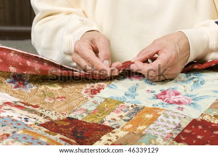 A woman stitches by hand the binding to finish a quilt. - stock photo