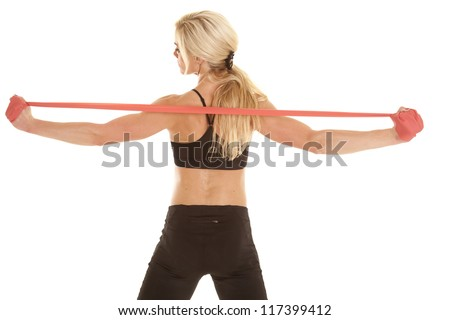 A woman stretching out her back and shoulders using her band - stock photo