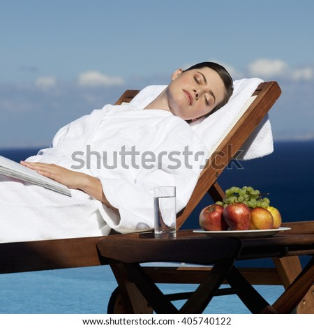 A woman sunbathing by a pool - stock photo