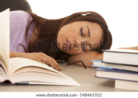 a woman surrounded by books asleep on her desk. - stock photo