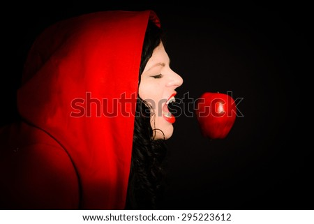 A woman takes a bite of the apple