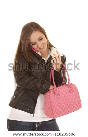 A woman talking on her phone while reaching into her pink purse. - stock photo