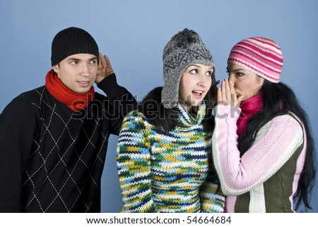 A woman tells her friend a secret at ear and she looks surprised while a man behind  them trying to hear what women say - stock photo