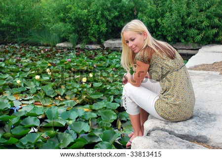 A woman thinking next to a lily pond - stock photo