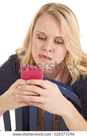 A woman thinking really hard while she is text-ing on her cell phone. - stock photo