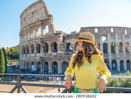 A woman tourist is standing, leaning against a banister, looking into the distance and smiling. She is delighted to be in Rome. In the distance, the Colosseum and tourists on a hot summer's day. - stock photo