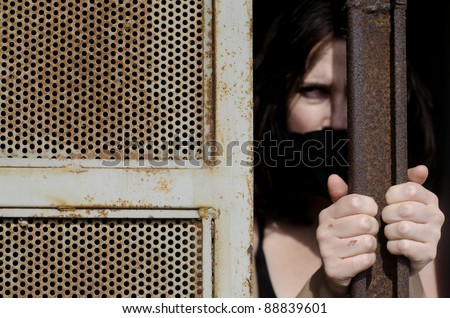 A woman trapped in a prison jail cell with a mouth cover - stock photo