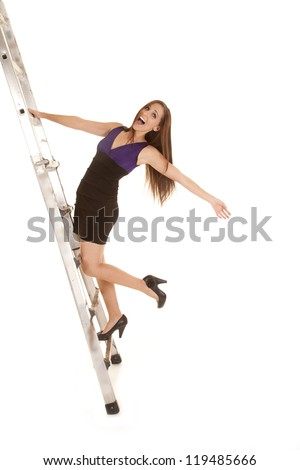 a woman trying to climb the ladder to success and feeling like she is going to fall. - stock photo