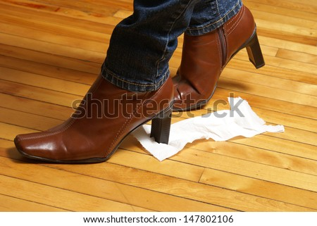 A woman unknowingly tracks a piece of toilet paper on the bottom of her boot which makes for an embarrassing time. - stock photo