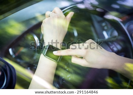 A woman uses smartwatch in the car. Smart watch concept. - stock photo