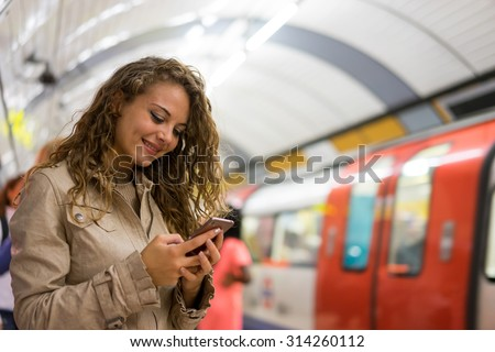 A woman using a mobile phone on the tube underground station, London - stock photo