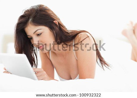 A woman using a tablet pc while lying on a bed with her legs crossed. - stock photo
