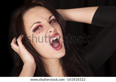 A woman vampire showing off her teeth with her mouth open. - stock photo
