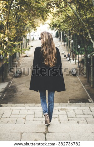 A woman walking down stairs in Barcelona, Spain - stock photo