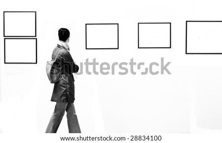 A woman walking in a photographic exhibition gallery - stock photo