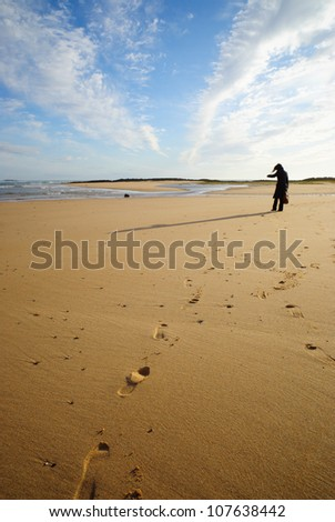 A woman walking on the beach, leaving footprints on the sand.
