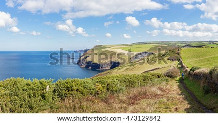 A woman walking the stunning North Cornwall coastline between Boscastle and Crackington Haven in England.