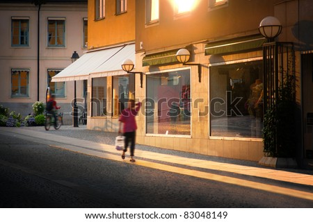 A woman walking with shopping bag in city at sunset