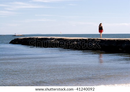 A woman walks down the jetty at the beach. - stock photo