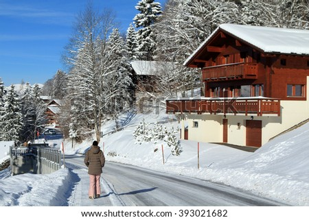 A woman walks through the streets of a quaint alpine village near a ski resort in the Swiss Alps, Switzerland. - stock photo