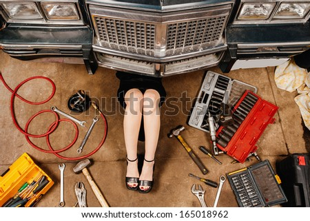 A woman wearing a black skirt and heels doing repairs under the front of an old car from the early 80's. - stock photo