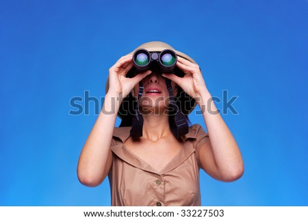 A woman wearing a pith helmet searching with a pair of binoculars, blue background with copy space. - stock photo