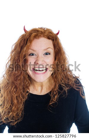 A woman wearing devil horns with a crazy expression on her face - stock photo