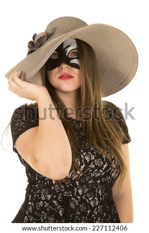 A woman wearing her mask and a hat, trying to hide. - stock photo