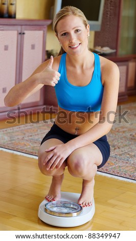 a woman weighs in on a bathroom scale, after a successful diet - stock photo