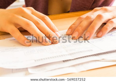 A woman while sorting her old receipts. - stock photo
