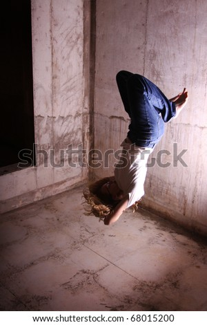 "A woman who appears to be falling to a painful injury. (The ""falling"" person is actually jumping up, and the photo has been flipped 180 degrees. What appears to be the floor is actually the ceiling.) - stock photo"