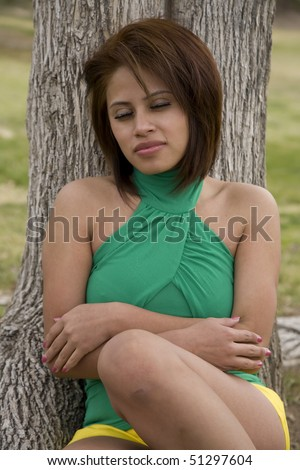A woman who has fallen asleep while sitting back against a tree in the outdoors.