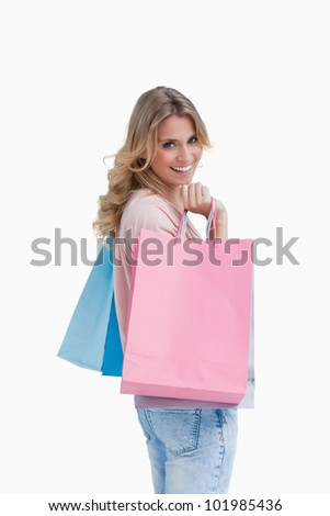 A woman who is carrying shopping bags is smiling at the camera - stock photo