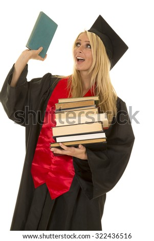 A woman who is graduating holding up a book with a smile on her face. - stock photo
