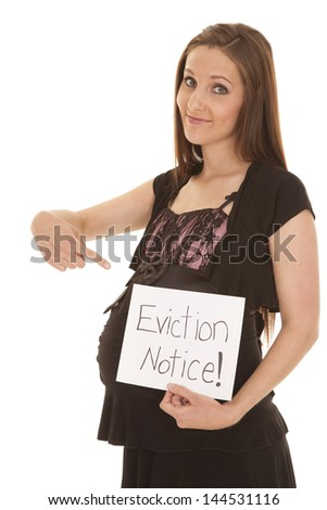 A woman with a big smile on her face pointing down at her belly and to the eviction notice - stock photo