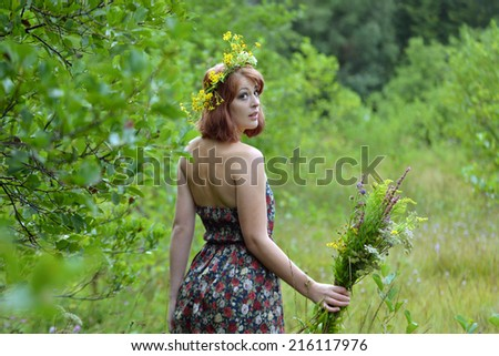 A woman with a bouquet of flowers and a wreath around her head - stock photo