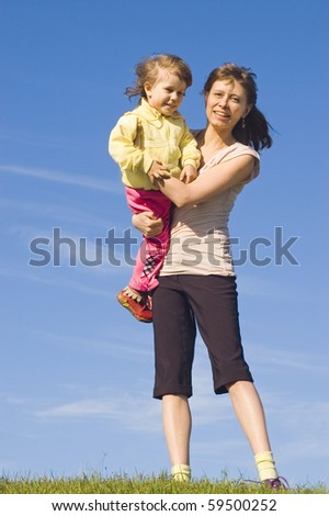 A woman with a child against the blue sky - stock photo