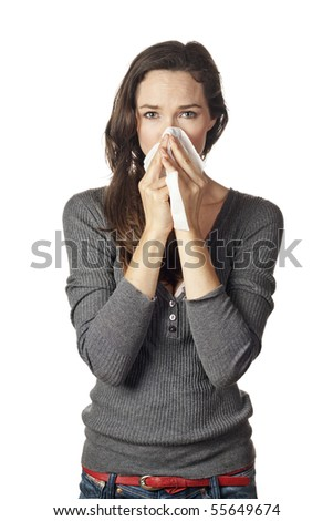 A woman with a cold or allergy wiping or blowing her nose. - stock photo