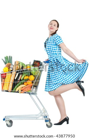 A woman with a full shopping cart happy to be shopping - on a white background - stock photo