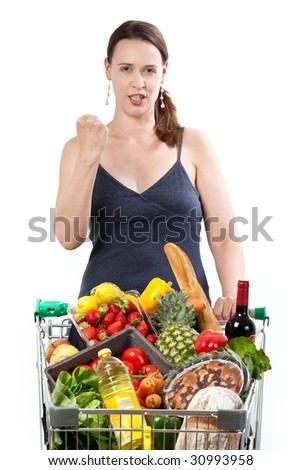 A woman with a full shopping cart happy to be shopping - punching the air on a white background. - stock photo